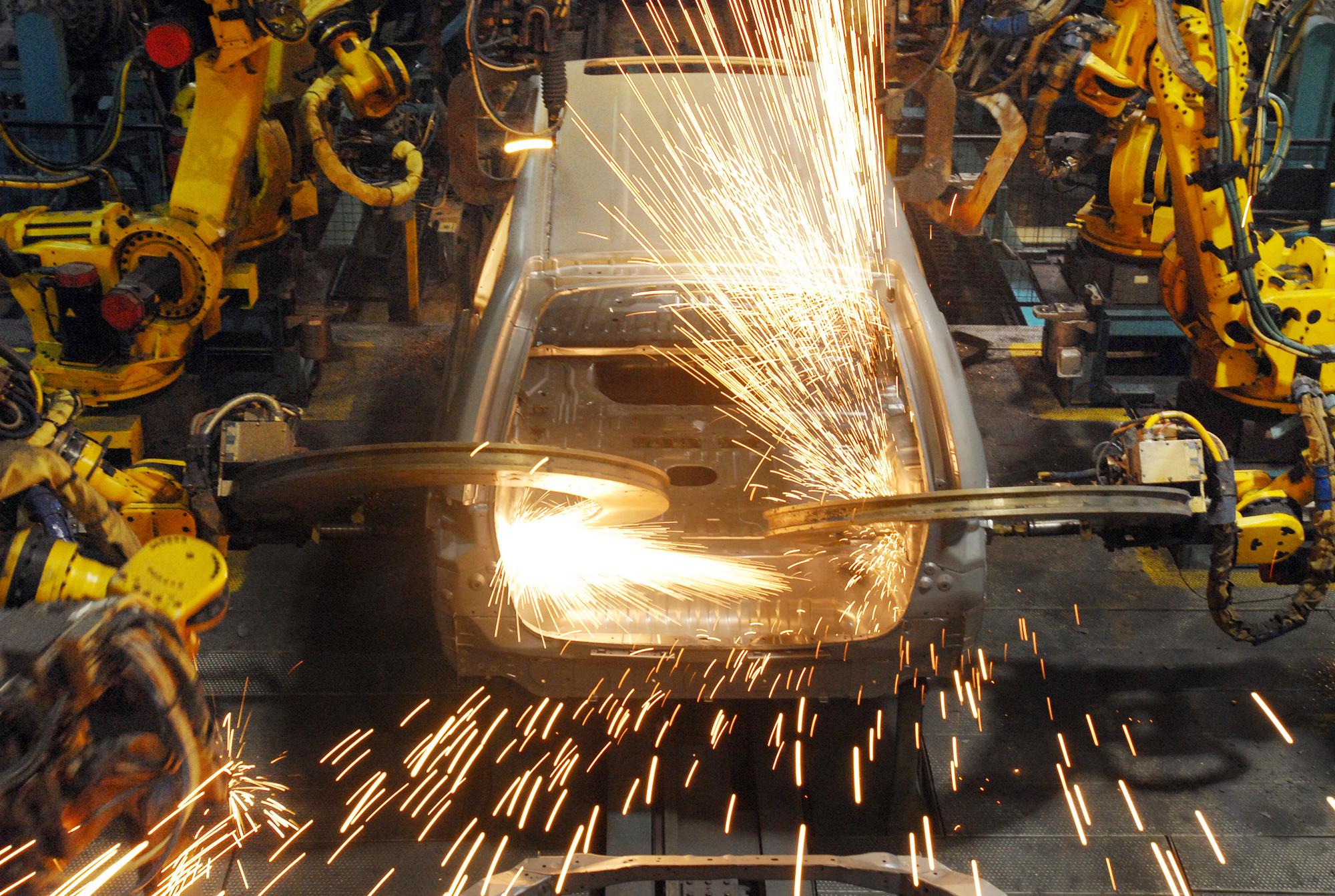 Автоматическая сварка с использованием роботов на заводе Хонда.